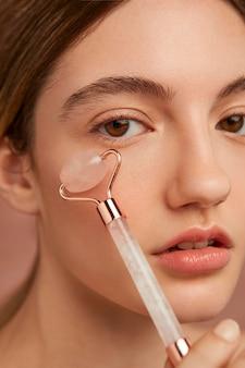 Bliska kobieta za pomocą narzędzia do twarzy