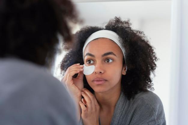 Bliska kobieta za pomocą opaski na oko