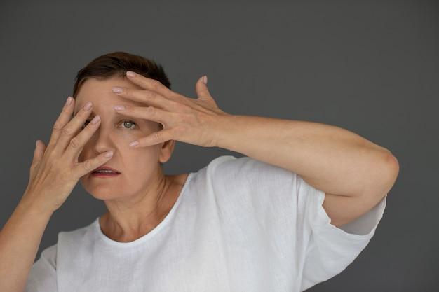 Bliska kobieta zakrywająca twarz