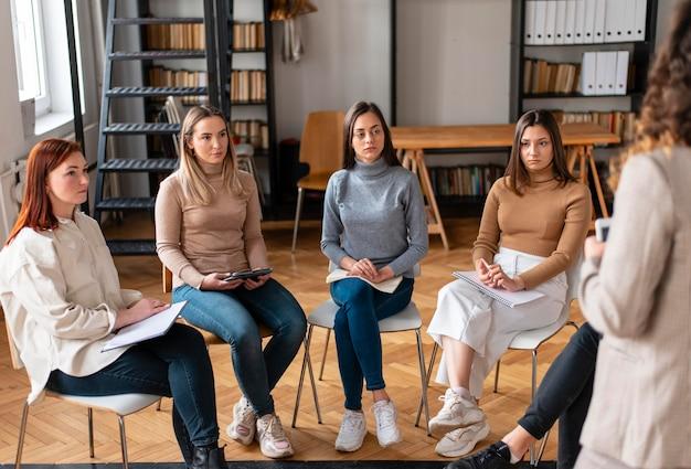 Bliska kobiety siedzące na krzesłach