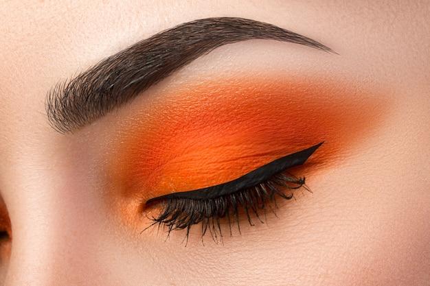 Bliska kobiety tworzą oko z pięknym pomarańczowym smokey oczy