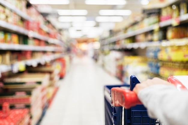 Bliska kobiety za pomocą koszyka w supermarkecie. rozmyte tło. koncepcja żywności na rynku.