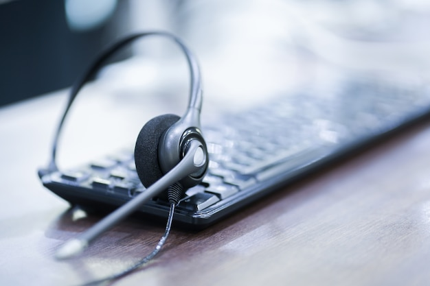 Bliska koncentrować się na urządzeniu zestawu słuchawkowego call center na biurku klawiatury komputera
