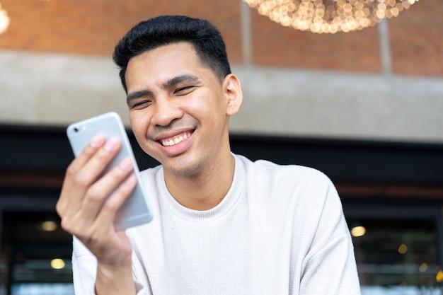 Bliska łacińskiej człowieka grać na koncepcji smartfona