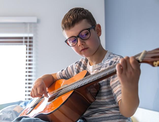 Bliska ładny chłopiec w okularach uczy się grać na gitarze klasycznej w domu.