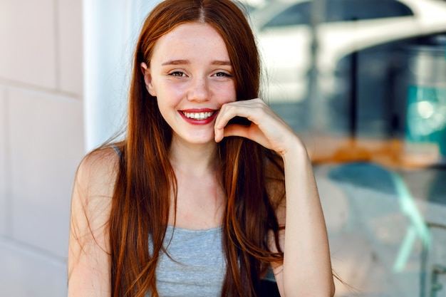 Bliska ładny portret ładnej rudowłosej kobiety, z niesamowitymi długimi włosami, świeżym naturalnym makijażem, dużym uśmiechem i oczami, pastelowymi delikatnymi kolorami, delikatnym, zmysłowym nastrojem.
