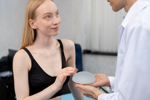 Bliska lekarz trzymający implant piersi