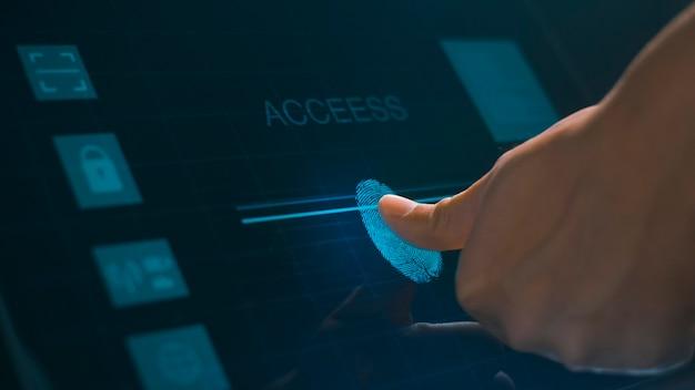 Bliska ludzki palec dotyka monitora komputera interfejsu, tożsamości biometrycznej odcisków palców i zatwierdzenia.