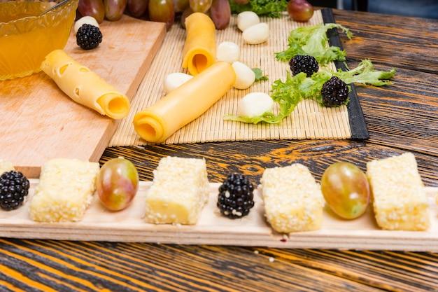 Bliska martwa natura żywności - wykwintne deski owoców i serów na rustykalnym drewnianym stole