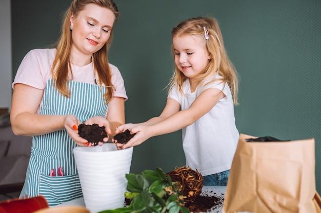 Bliska matka ubrana w fartuch i córka przeszczep roślin. szczęśliwa rodzina położyła ziemię w białym garnku. ogrodnictwo domowe, wspólnota.