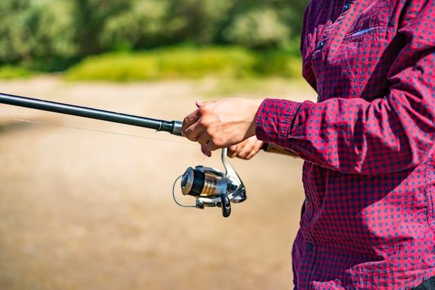 Bliska męskie ręce łowienie ryb z przędzenia na brzegu rzeki.