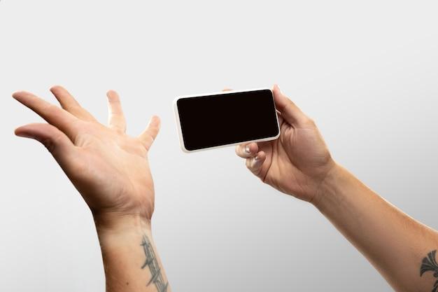 Bliska męskie ręce trzymając telefon z pustego ekranu podczas oglądania online popularnych meczów sportowych i mistrzostw. miejsce na reklamę. nowe zasady bezpieczeństwa. koncepcja urządzeń, gadżetów, technologii.
