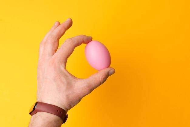Bliska męskiej ręki trzymającej różowe jajko wielkanocne