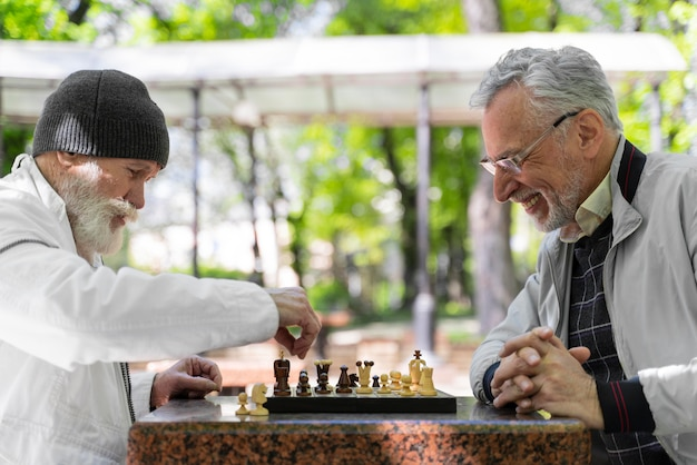 Bliska mężczyzn grających w szachy na zewnątrz