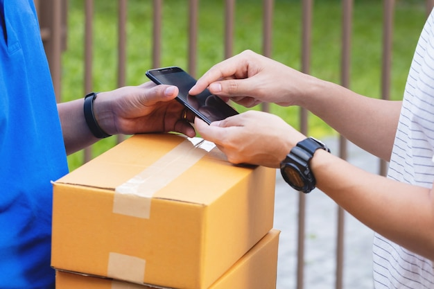 Bliska mężczyzna ręce dołączając podpis w cyfrowym telefonie komórkowym po otrzymaniu paczki od kuriera w domu. zakupy online