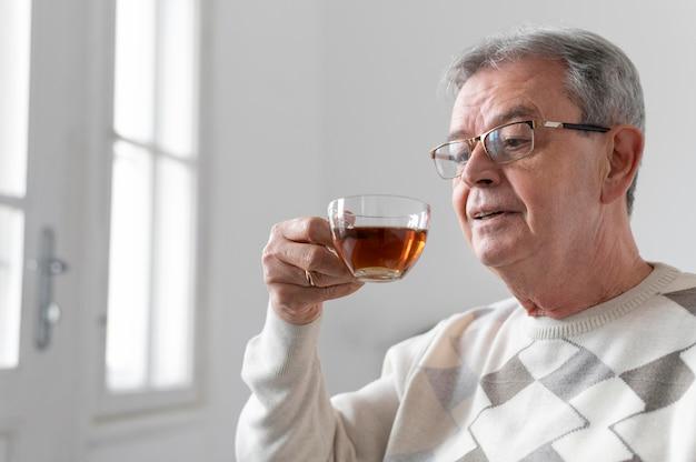 Bliska mężczyzna trzyma filiżankę herbaty