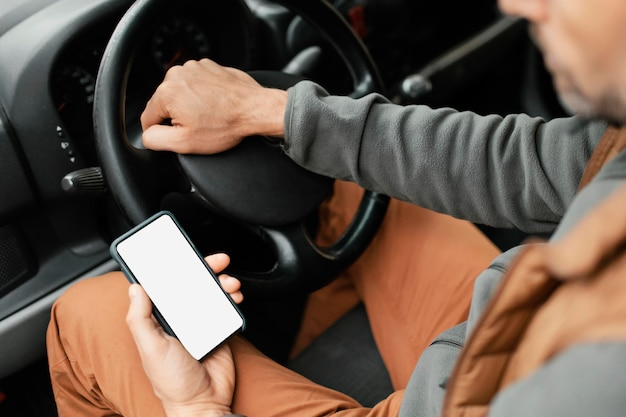 Bliska mężczyzna w samochodzie z telefonem komórkowym