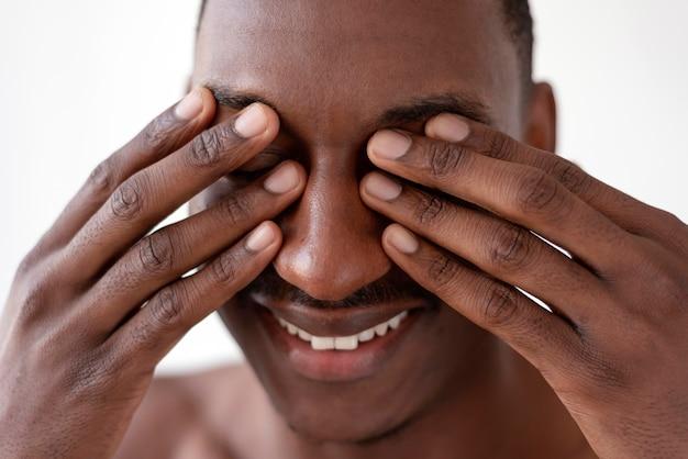 Bliska mężczyzna zasłaniający oczy
