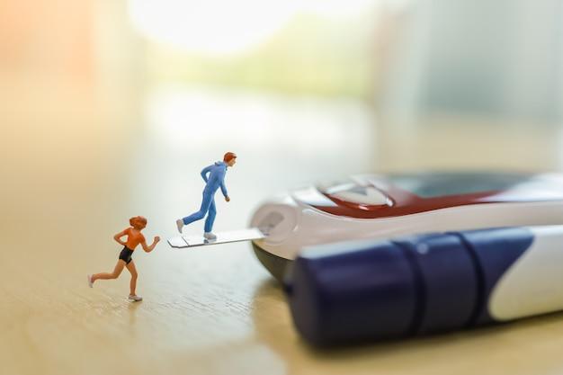 Bliska mężczyzny i kobiety biegacza miniaturowa postać działa na pasek testowy cukru we krwi i podłącz do glukometru na drewnianym stole.