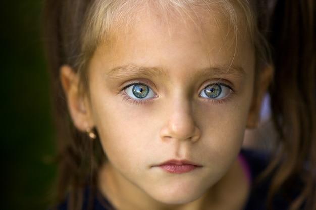Bliska, miękki, skupiony portret ładnej, inteligentnej, kaukaskiej, małej dziewczynki o pięknych, dużych oczach i brązowych długich włosach, wyglądającej pewnie