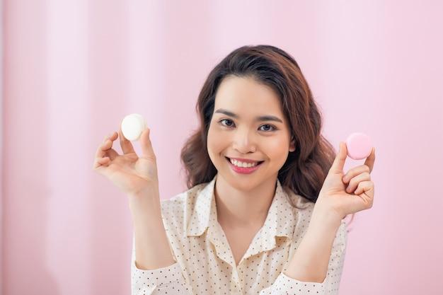 Bliska młoda kobieta azjatyckich jeść macarons ciasta przed różową ścianą.