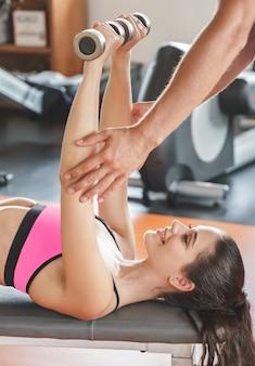 Bliska młoda kobieta podnoszenia ciężarów treningu wspomagana przez jej trenera na siłowni