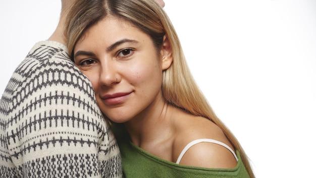 Bliska młoda kobieta rasy kaukaskiej z długimi farbowanymi włosami, kolczykiem w nosie i pięknymi rysami, patrząca z subtelnym uśmiechem, opierająca głowę na piersi nierozpoznawalnego mężczyzny w swetrze