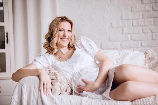 Bliska młoda kobieta w ciąży, leżąc na kanapie