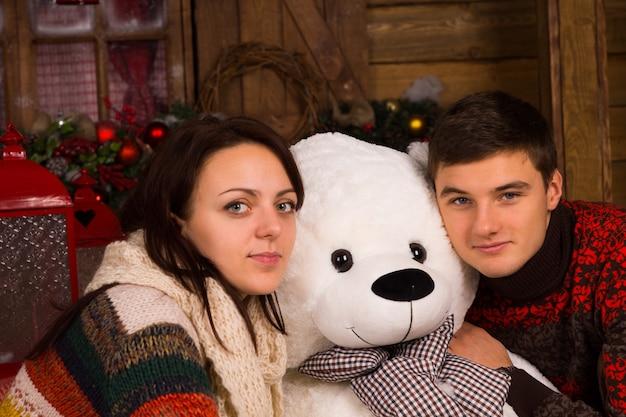 Bliska młoda para biały w zimowe stroje przytulanie lalka biały niedźwiedź, patrząc w kamerę.