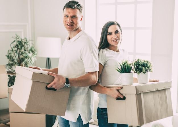 Bliska młoda para układa pudełka w swoim nowym mieszkaniu