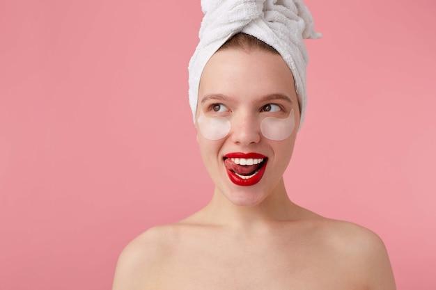 Bliska młoda uśmiechnięta dama po prysznicu z ręcznikiem na głowie, z plamami i czerwonymi ustami, odwraca wzrok i czuje się szczęśliwa, wstaje.