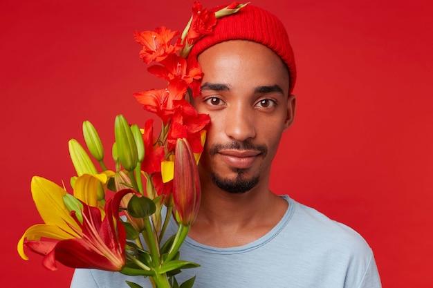 Bliska młody atrakcyjny facet w czerwonym kapeluszu i niebieskiej koszulce, trzyma bukiet w dłoniach, patrzy w kamerę z uspokajającym wyrazem i uśmiechnięty, stoi na czerwonym tle.