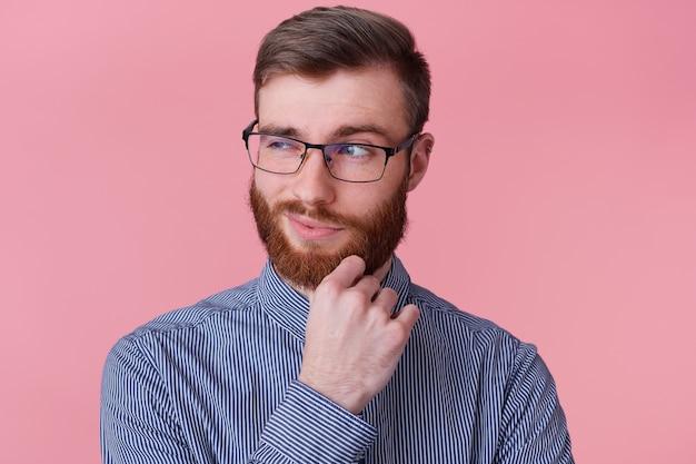 Bliska młody brodaty biznesmen z poważnym wyrazem twarzy myśli o pytaniu, w zamyśleniu dotykając brodę, patrząc w dal na białym tle na różowym tle.
