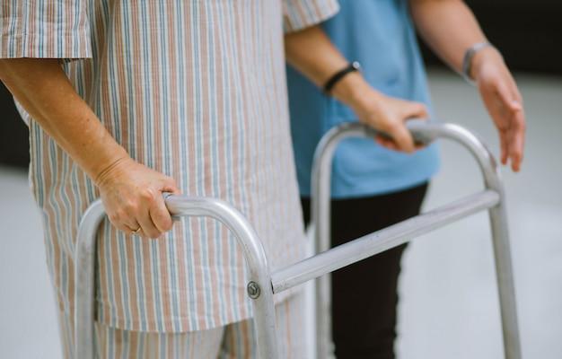 Bliska młody fizjoterapeuta pomaga starszemu pacjentowi za pomocą chodzika podczas rehabilitacji