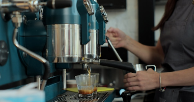 Bliska młody kaukaski kobiece barista pracownik przygotowuje napój kawowy w pobliżu ekspres do kawy serwujący gorące napoje w nowoczesnej kawiarni. zawód. usługi napojów.