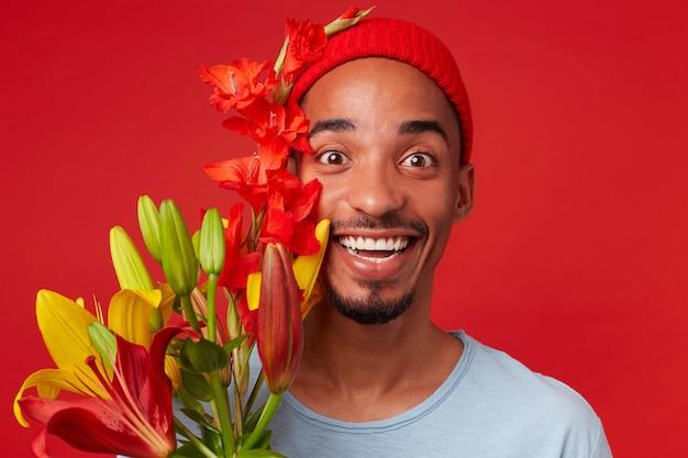 Bliska młody wesoły atrakcyjny facet w czerwonym kapeluszu i niebieskiej koszulce, trzyma bukiet w dłoniach, patrzy w kamerę z wyrazem zadowolenia i szeroko uśmiechnięty, stoi na czerwonym tle.
