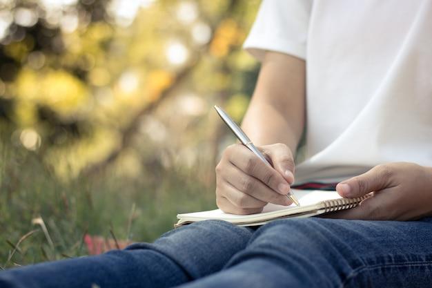 Bliska młodych kobiet pisania na notebooka w parku, koncepcja w edukacji i wiedzy