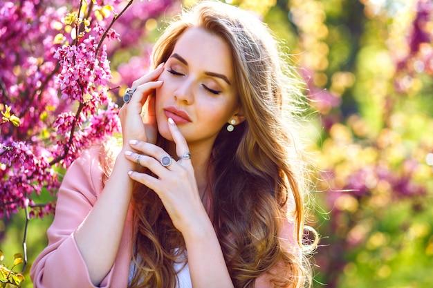 Bliska moda portret delikatnej eleganckiej ładnej kobiety z dużym zielonym tak i pełnymi ustami, naturalnym świeżym makijażem i długimi puszystymi włosami, malować schludne kwitnące drzewo sakura, słoneczny czas wiosny.
