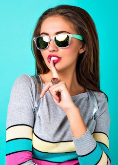 Bliska moda portret eleganckiej ładnej kobiety, seksowna twarz jasny makijaż, stylowy sweter na co dzień, pastelowe kolory wiosny, położyć palec na ustach.