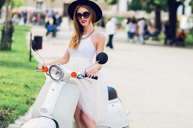 Bliska moda portret młodej kobiety blondynka w białej tiulowej spódnicy i czarnych obcasach siedzi na vintage skuter.