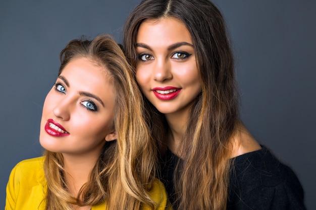 Bliska moda portret niesamowitej blondynki i brunetki, idealna skóra, jasny makijaż, czyste piękno, pełne seksowne czerwone usta, styl jesienno-zimowy,
