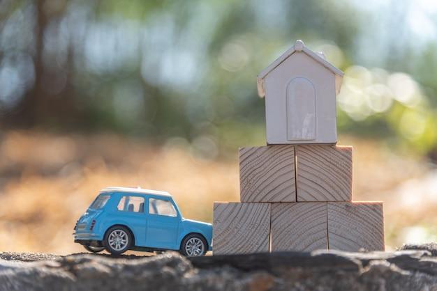 Bliska modelu domu i samochodu zabawki z drewnianymi klockami na zielonych drzewach i tle światła słonecznego. (selektywne skupienie)