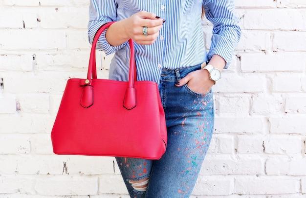 Bliska modna kobieta z czerwoną dużą torbą i akcesoriami do zegarka. koncepcja mody