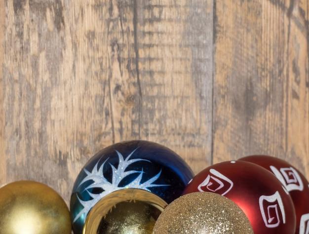 Bliska multi kolorowe błyszczące kulki na niewyraźne drewniane tła. ozdoby świąteczne