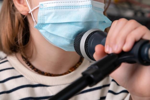 Bliska muzyk noszenie maski medyczne i trzymając mikrofon.