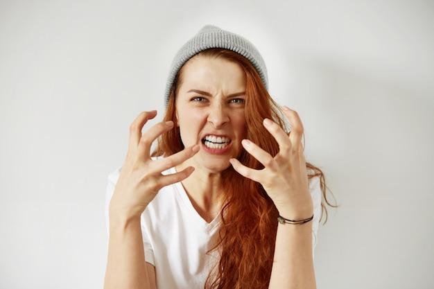Bliska na białym tle portret młodej zdenerwowanej kobiety zły, trzymając się za ręce w wściekłym geście