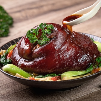 Bliska nalewania pikantnego sosu sojowego łyżką na tajwańskie jedzenie duszone jedzenie golonki wieprzowej w talerzu na rustykalnym stole