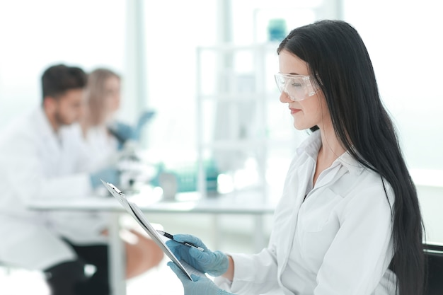 Bliska naukowiec kobieta czytanie notatek w dzienniku laboratoryjnym