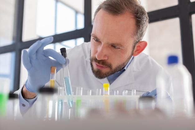 Bliska naukowiec patrząc na probówkę
