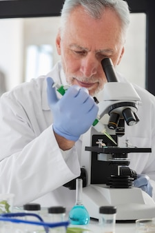 Bliska naukowiec patrząc przez mikroskop